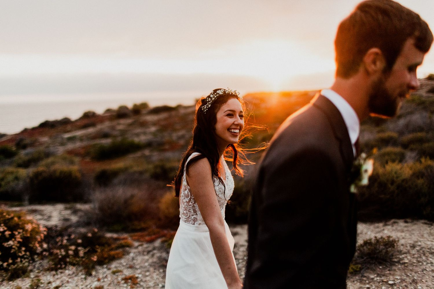 bride looking at groom while walking during golden hour