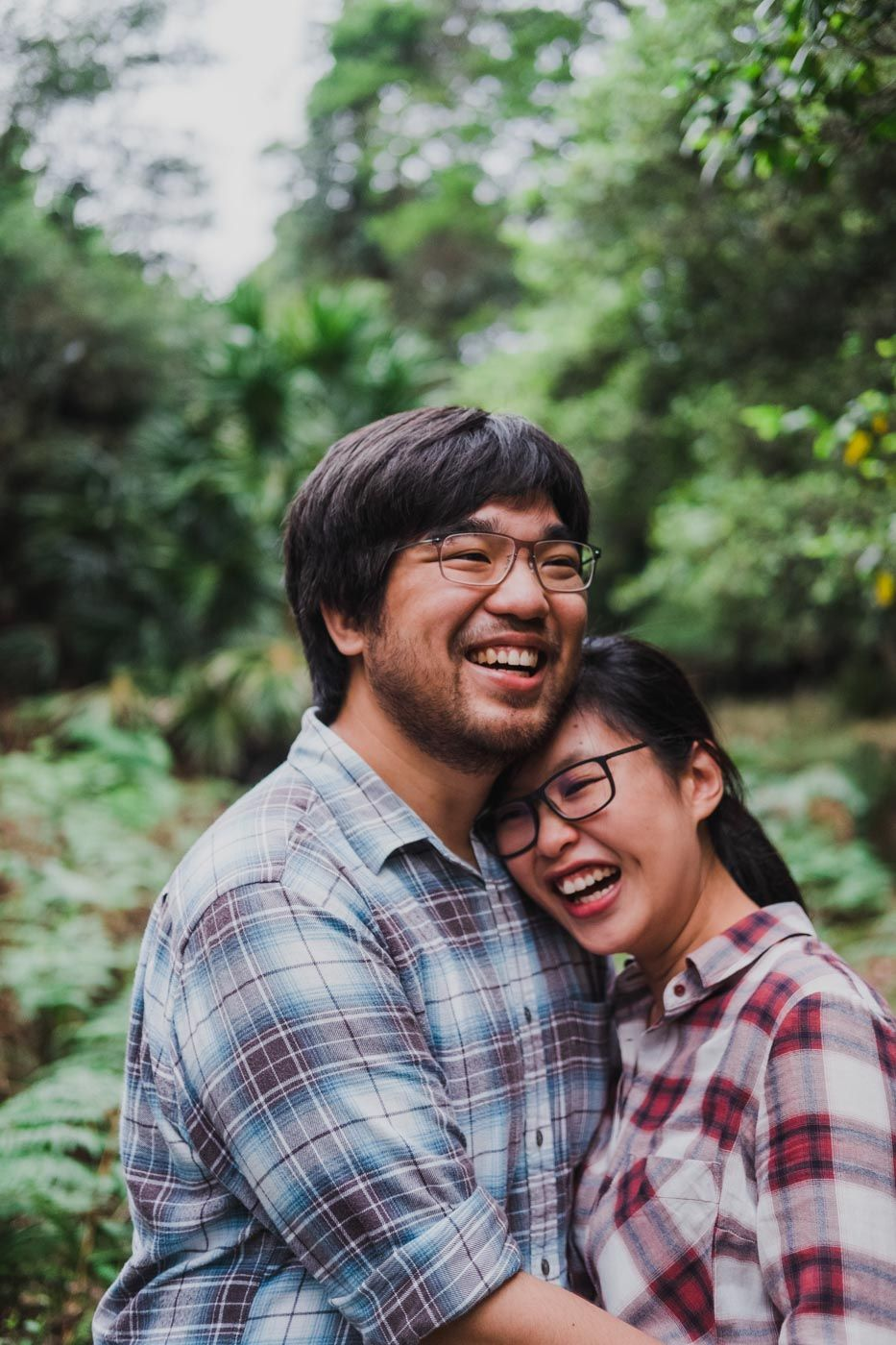 Couple laughing as they hold each other in the forest