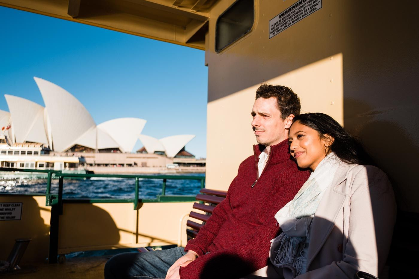 Woman resting her head on her partners shoulder on a ferry in Sydney with the Sydney Opera House in background