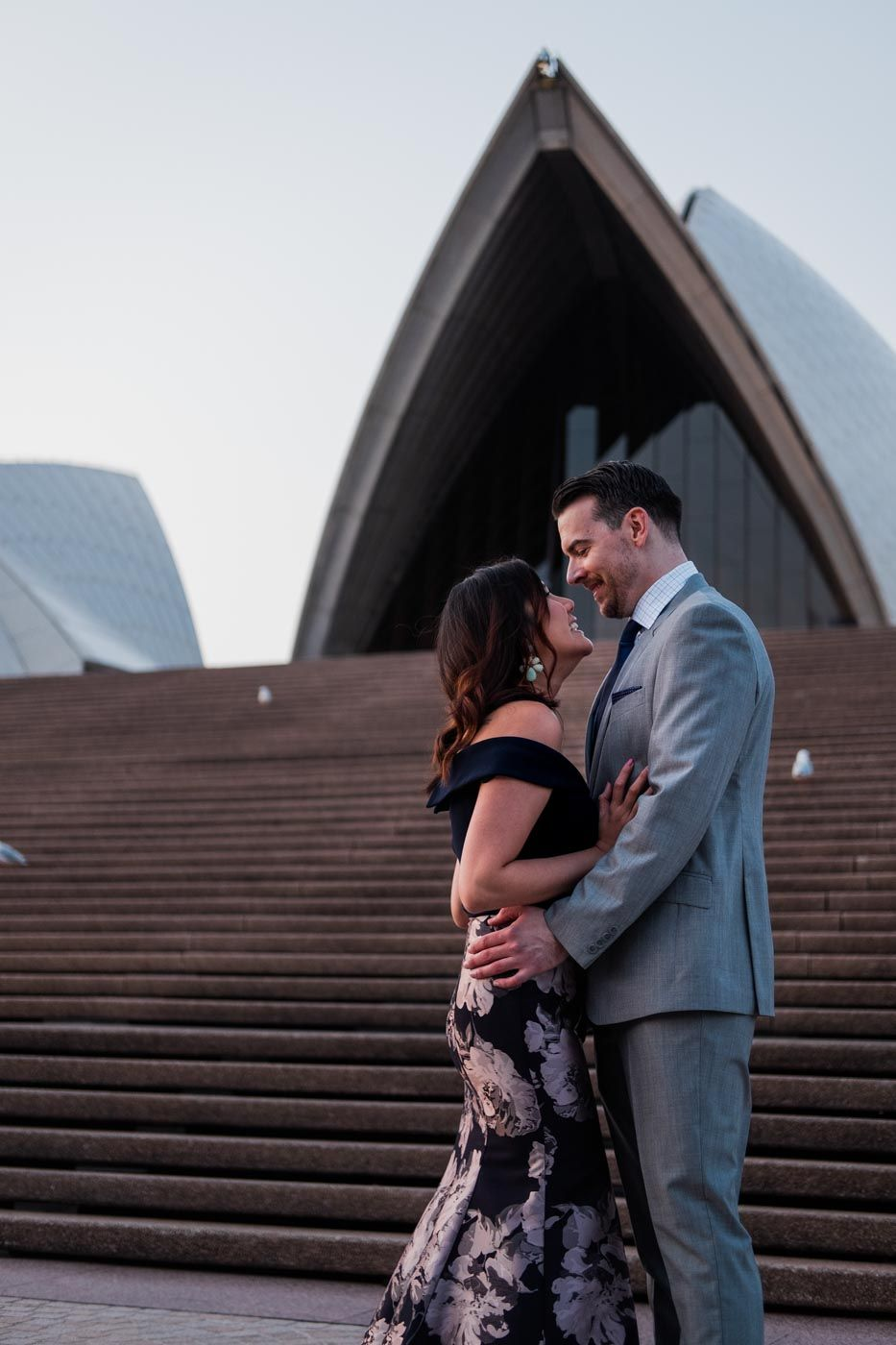 Couple sharing a laugh on the steps on the Sydney Opera House