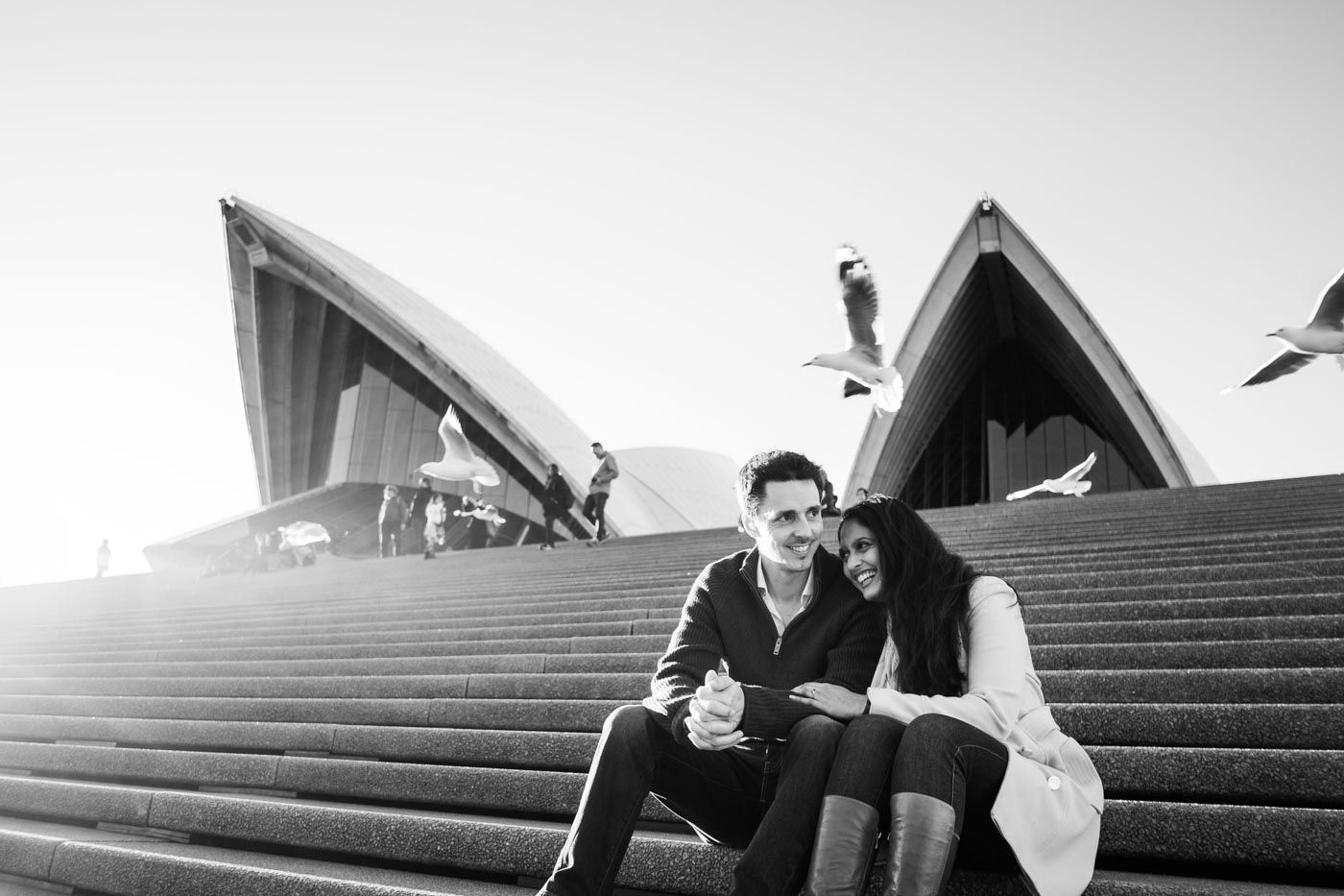 Couple sharing a laugh sitting on the Sydney Opera House steps with seagulls flying overhead