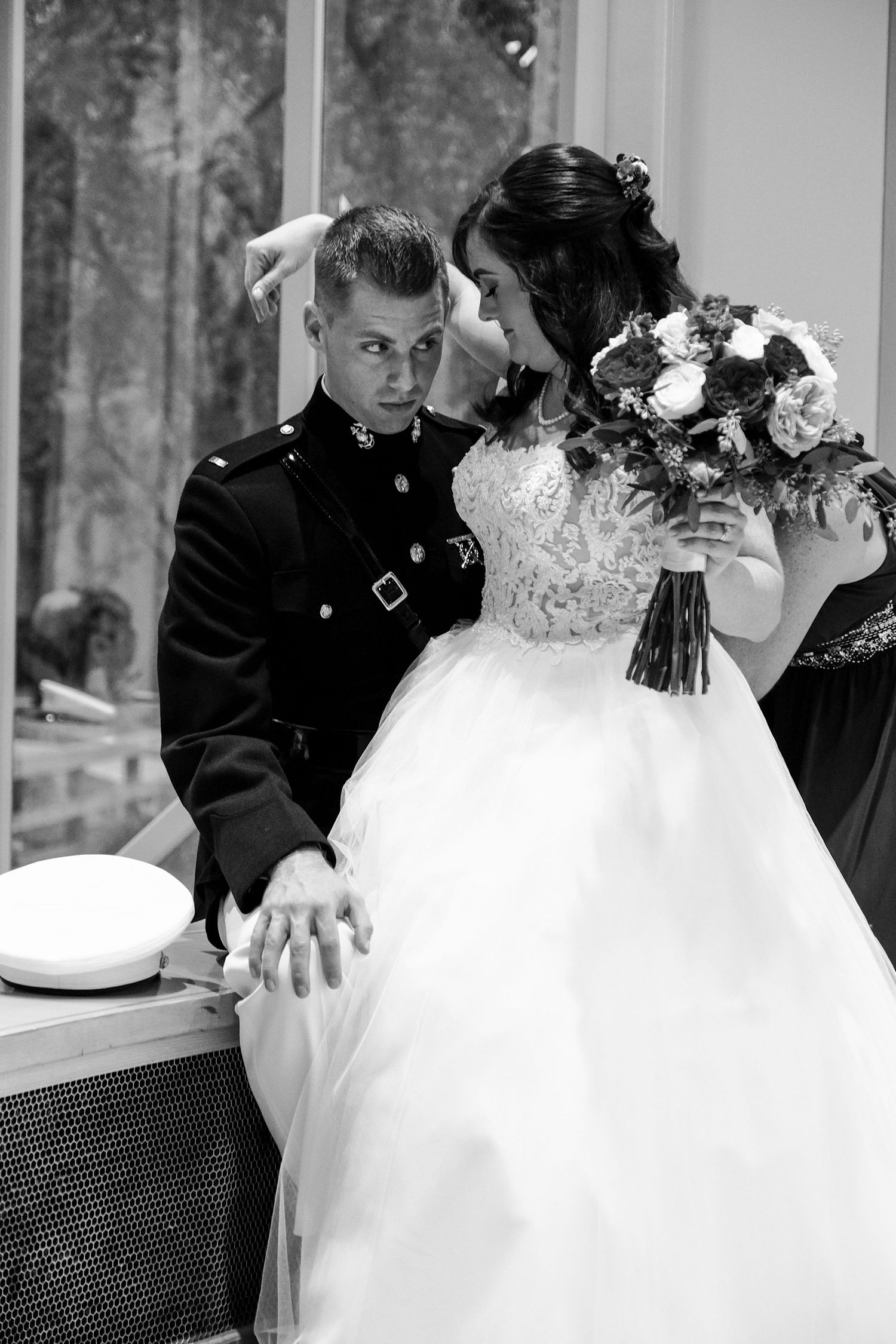 Black and white photograph of a bride sitting on the grooms lap after their wedding at the Baughman Center.