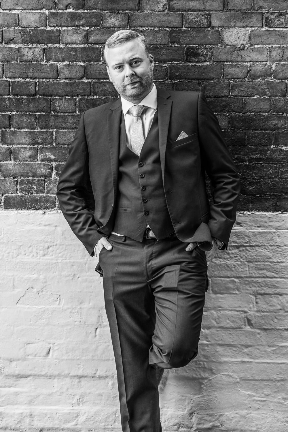groom against brick wall on one leg, Robert Nelson Wedding Photography