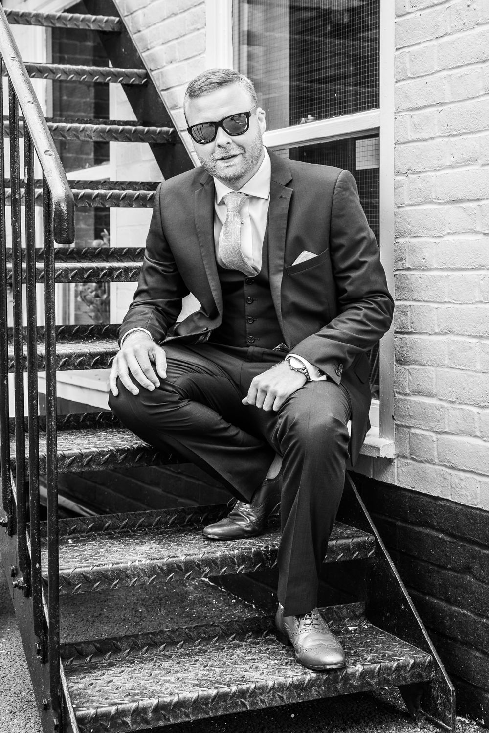 cool looking groom sitting on the stairs in black and white, Robert Nelson Wedding Photography