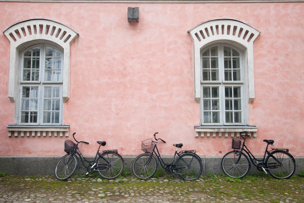 Pink walls with two bikes on it in Suomenlinna Finland