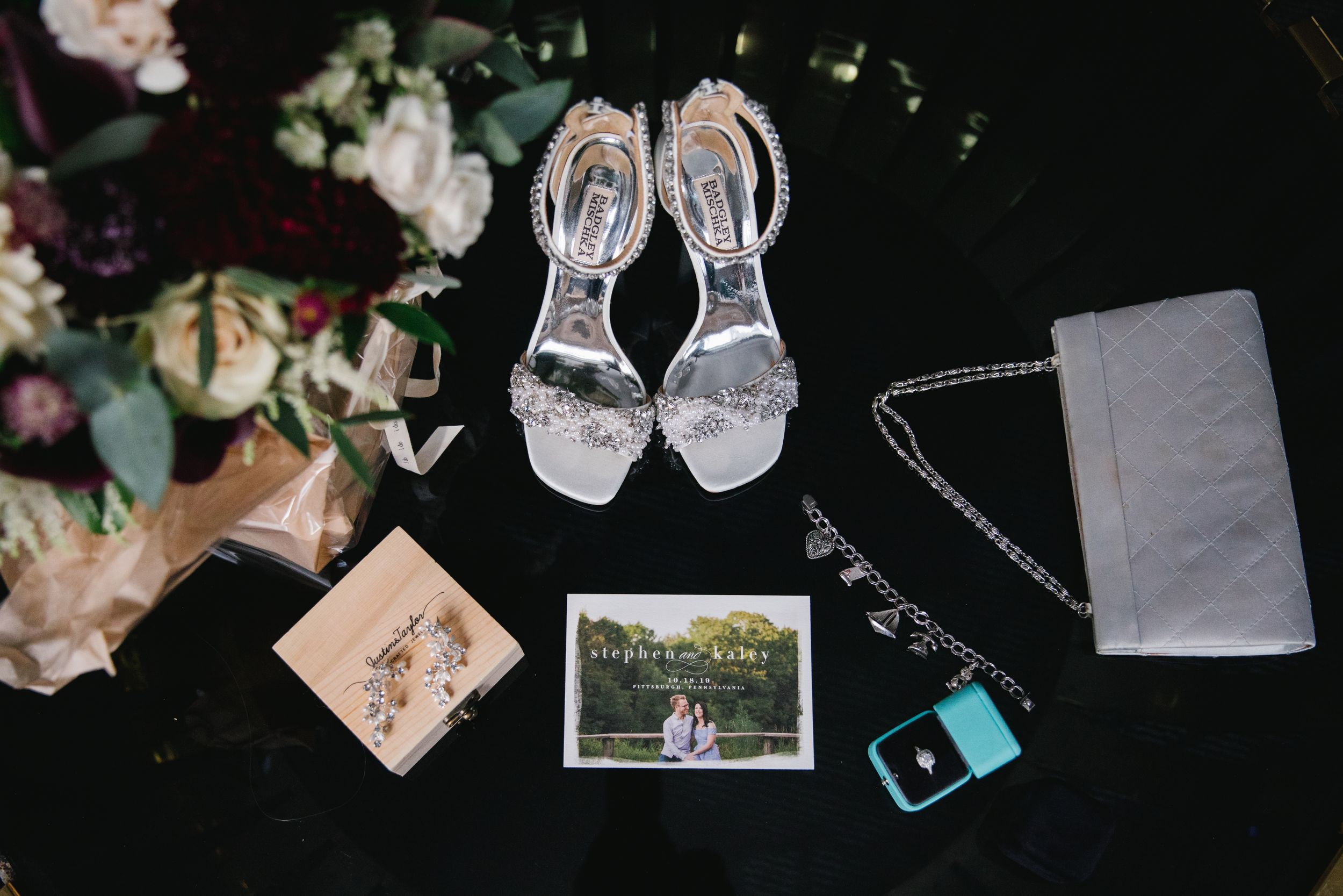 flat lay wedding details on black table top