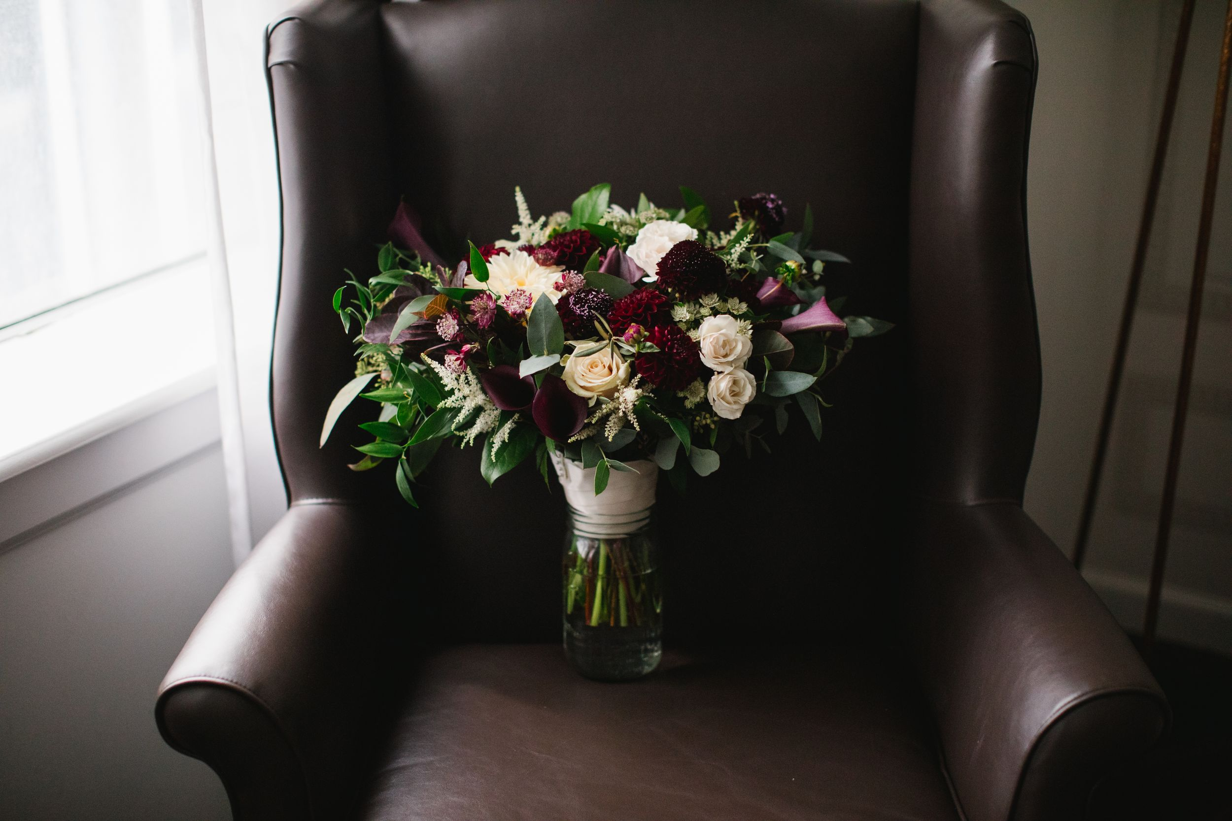 burgundy bridal floral bouquet on brown leather armchair