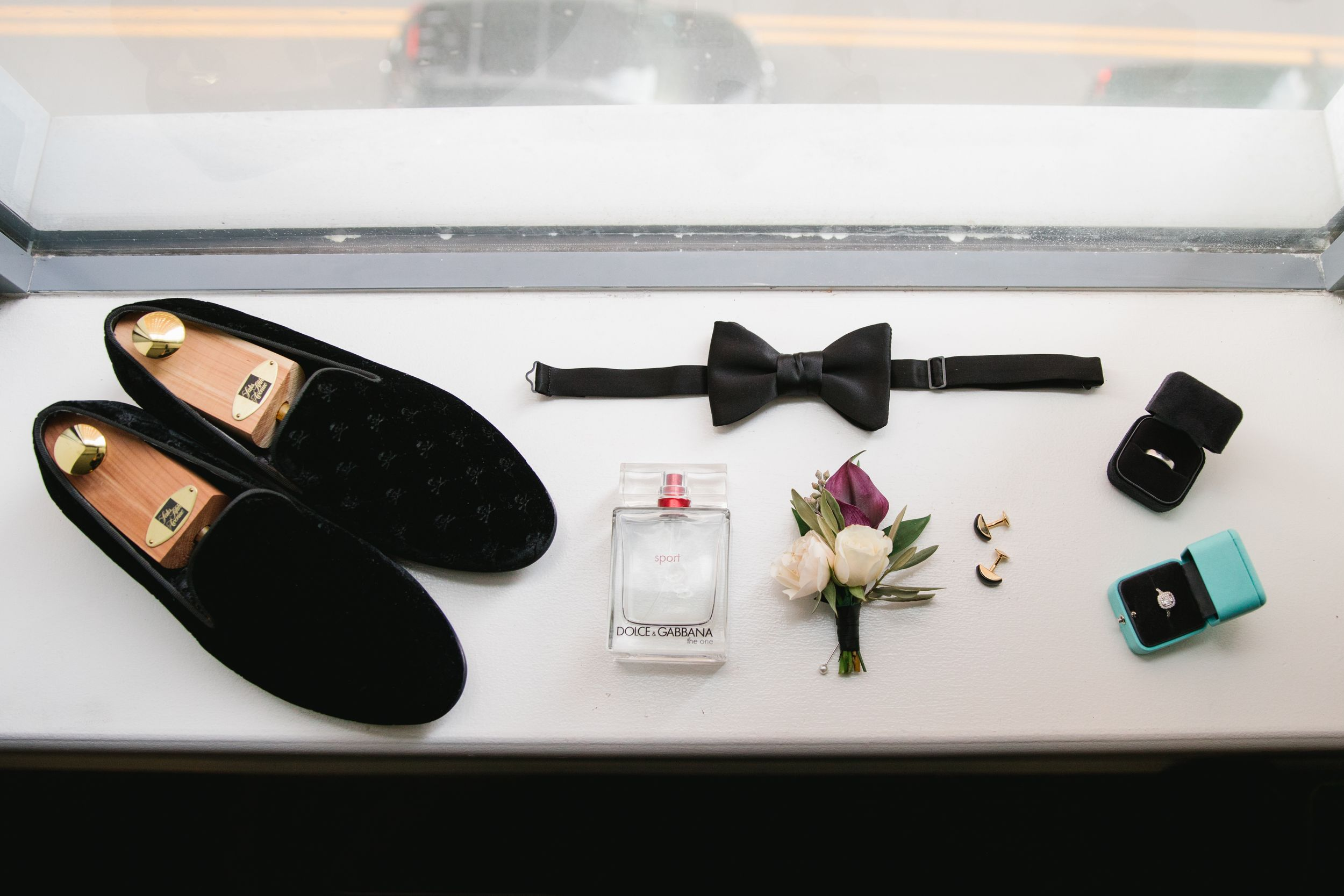 groomsman details flatlay - shoes, boutonniere, cologne, cufflinks, rings.