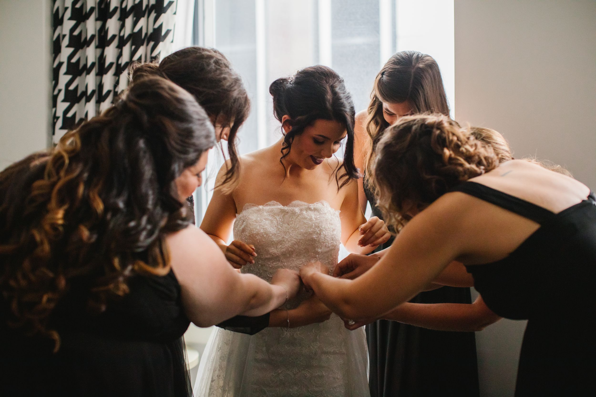 bridesmaids helping put on wedding skirt in front of window