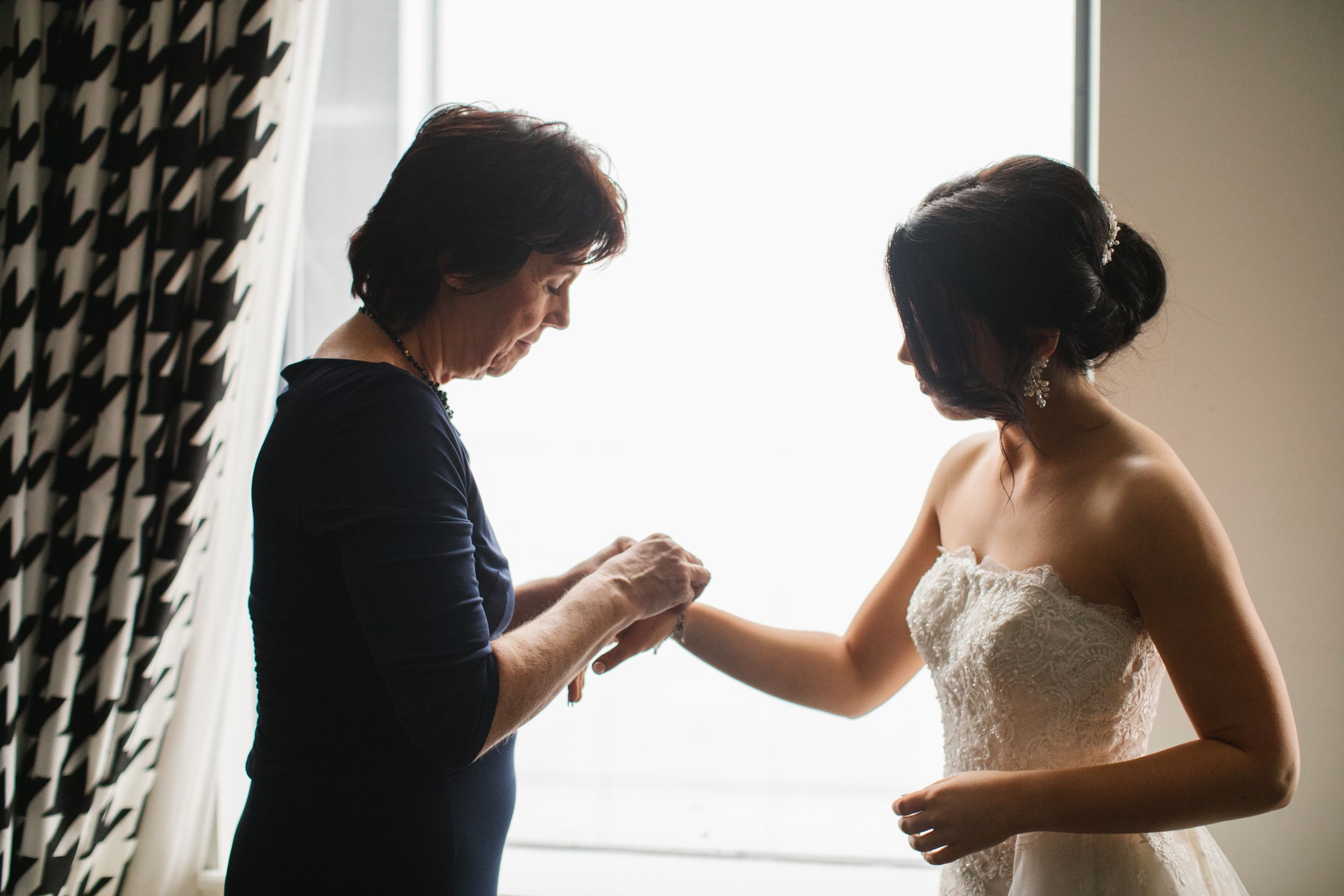 bride and mother of bride standing in front of window putting on jewellery