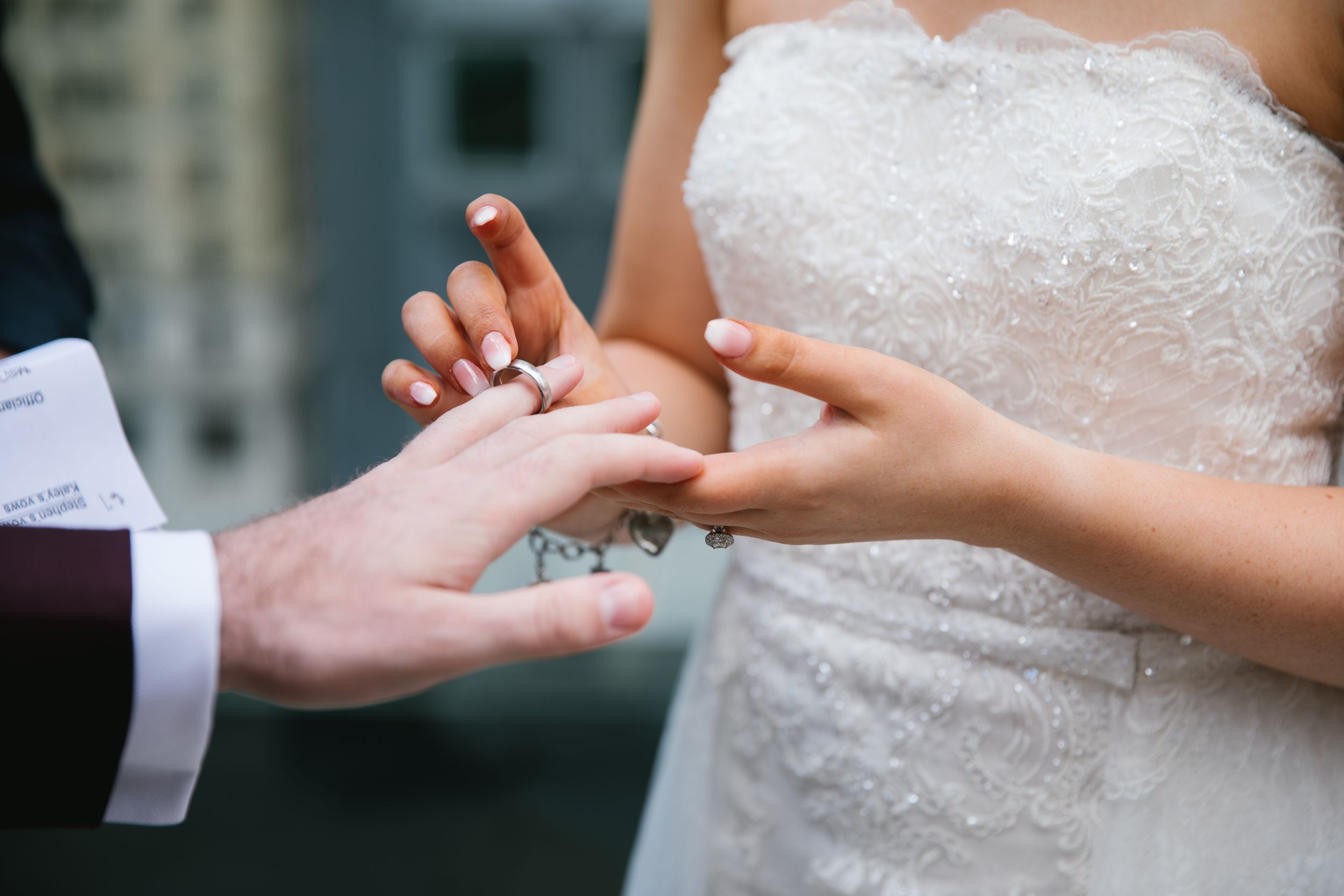 close up of exchanging rings during rooftop ceremony