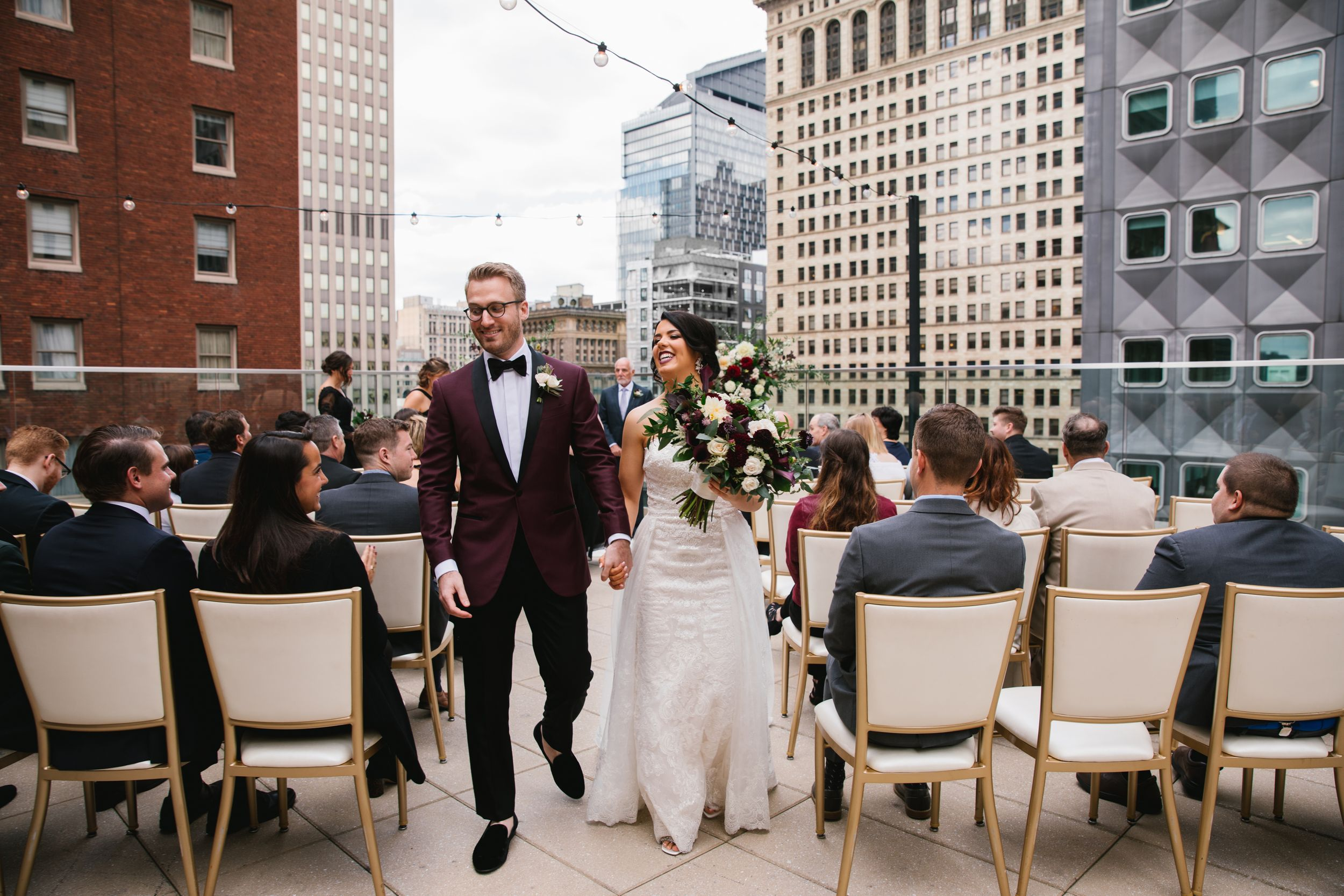 bride and groom walking down the aisle during rooftop ceremony laughing and holding hands