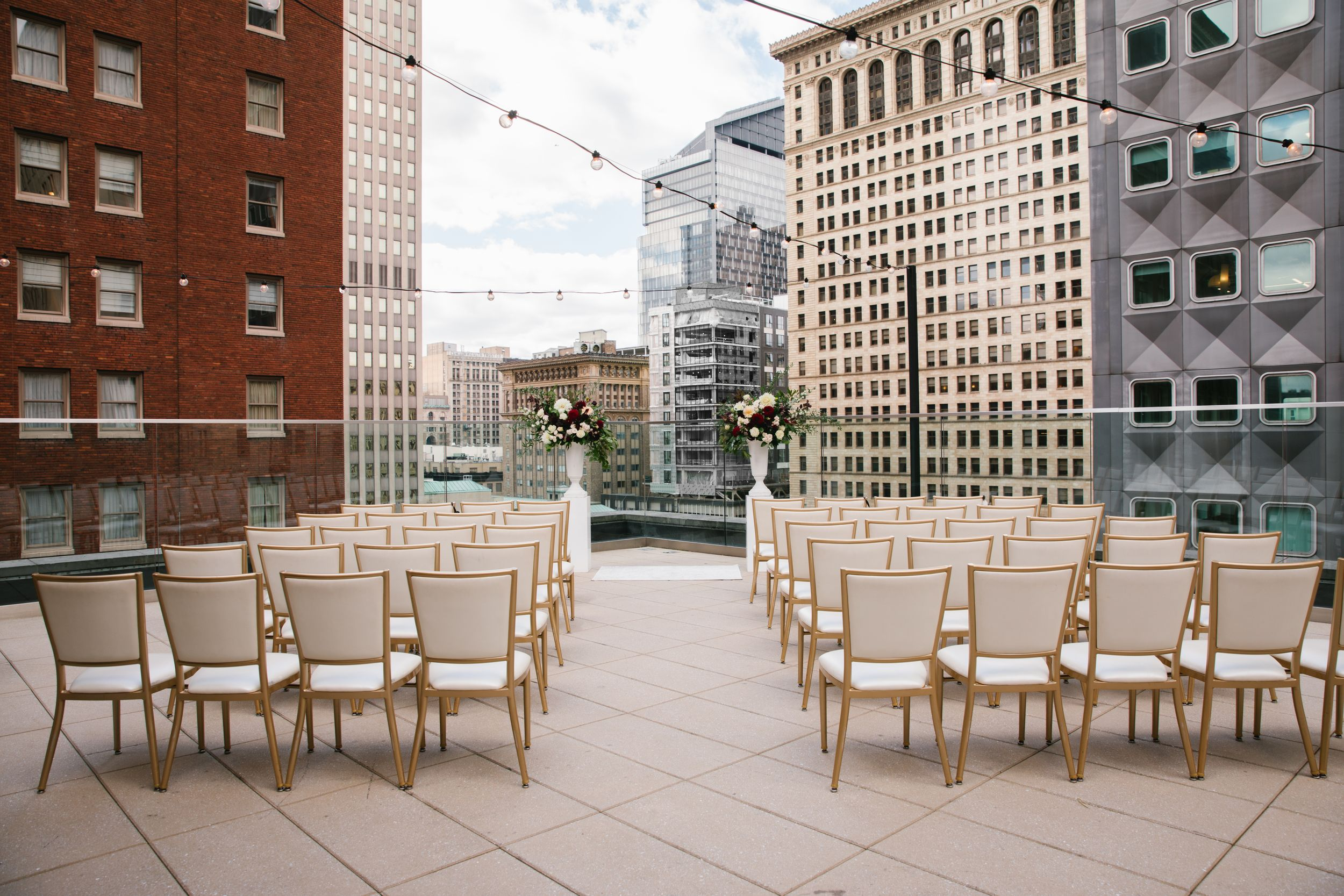 rooftop ceremony space overlooking the city with high rise buildings with string lights, column planters and gold chairs