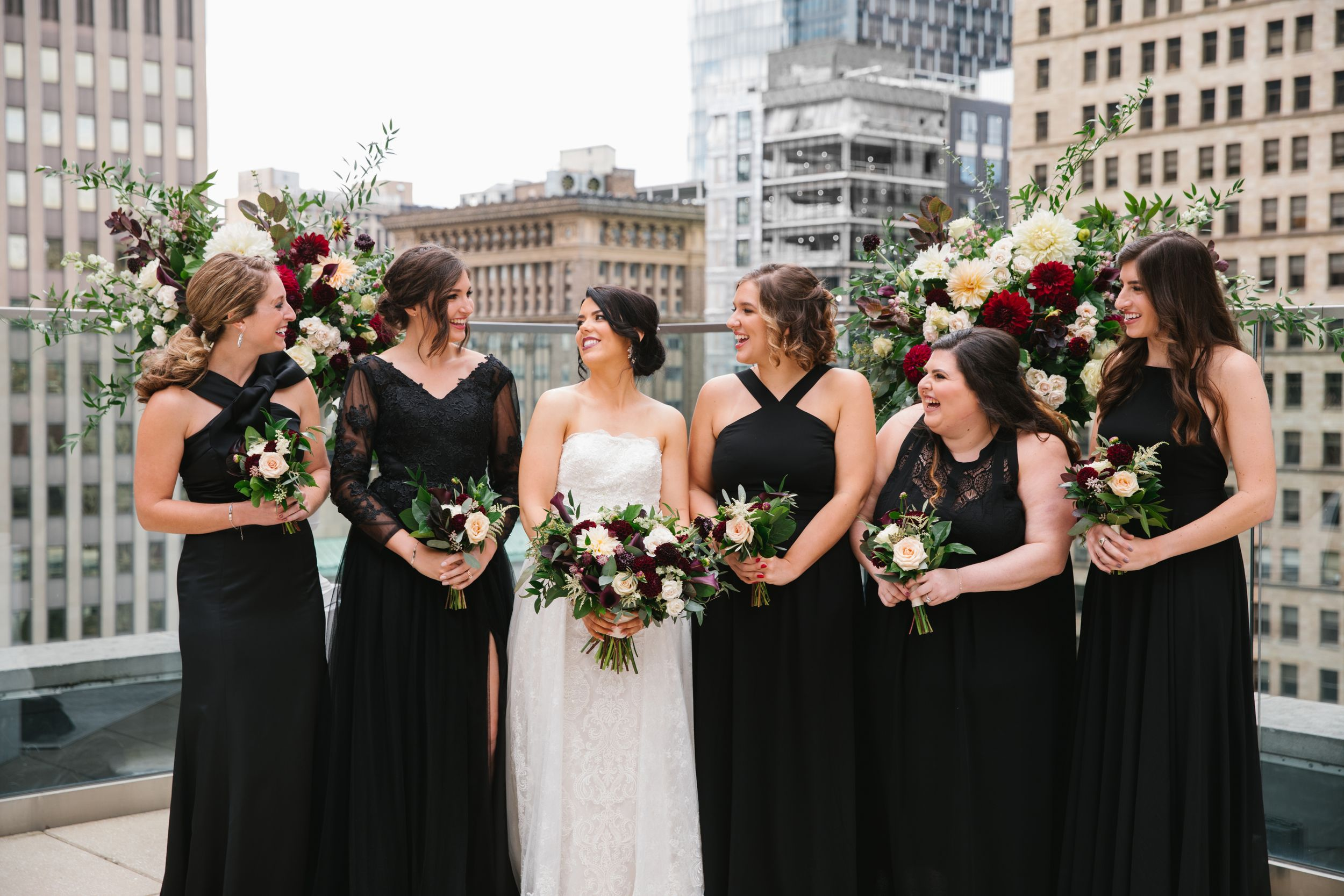 bride and bridesmaids in black dresses holding burgundy bouquets and laughing with city scape in the background