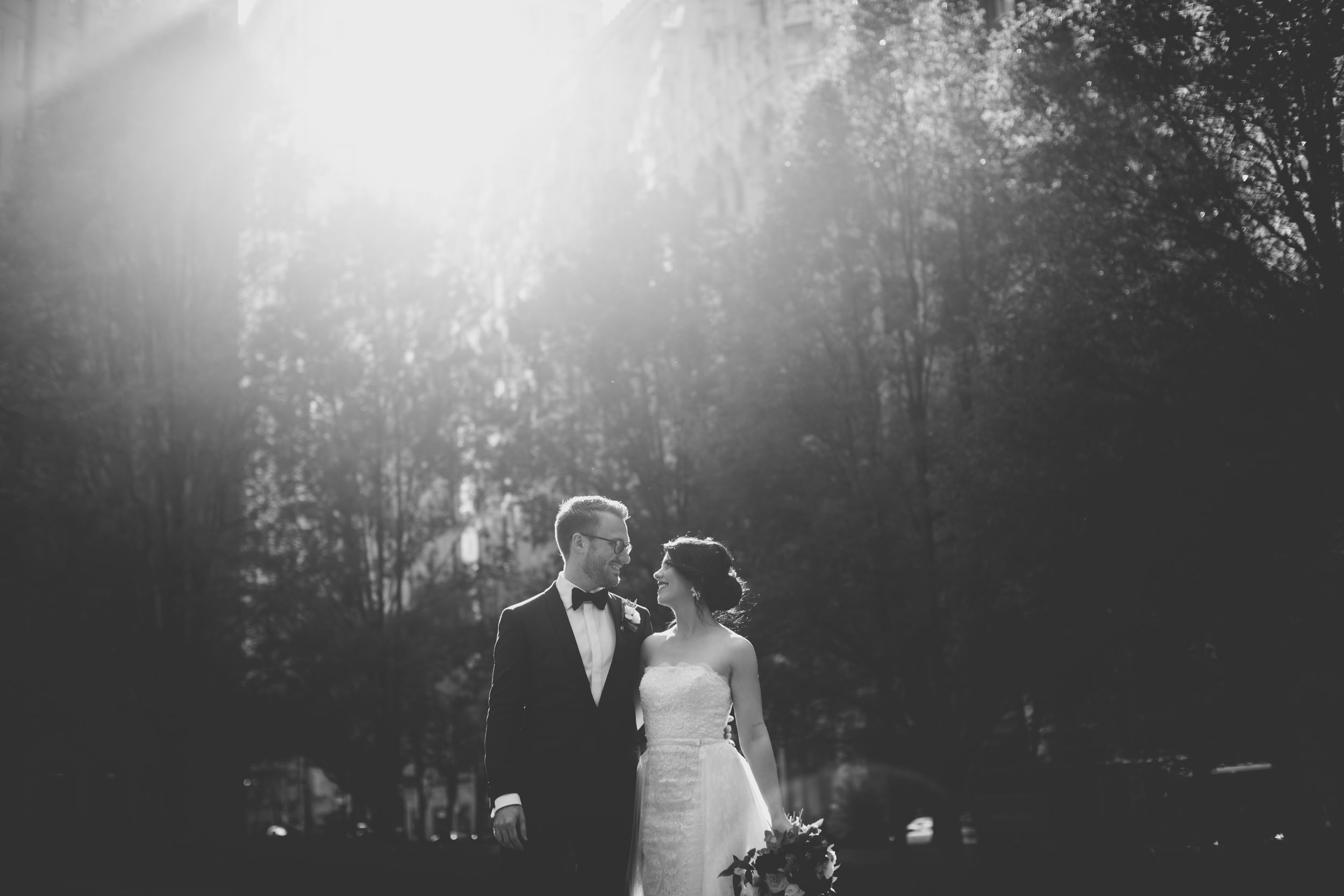 black and white photo of bride and groom with the sun shining on them