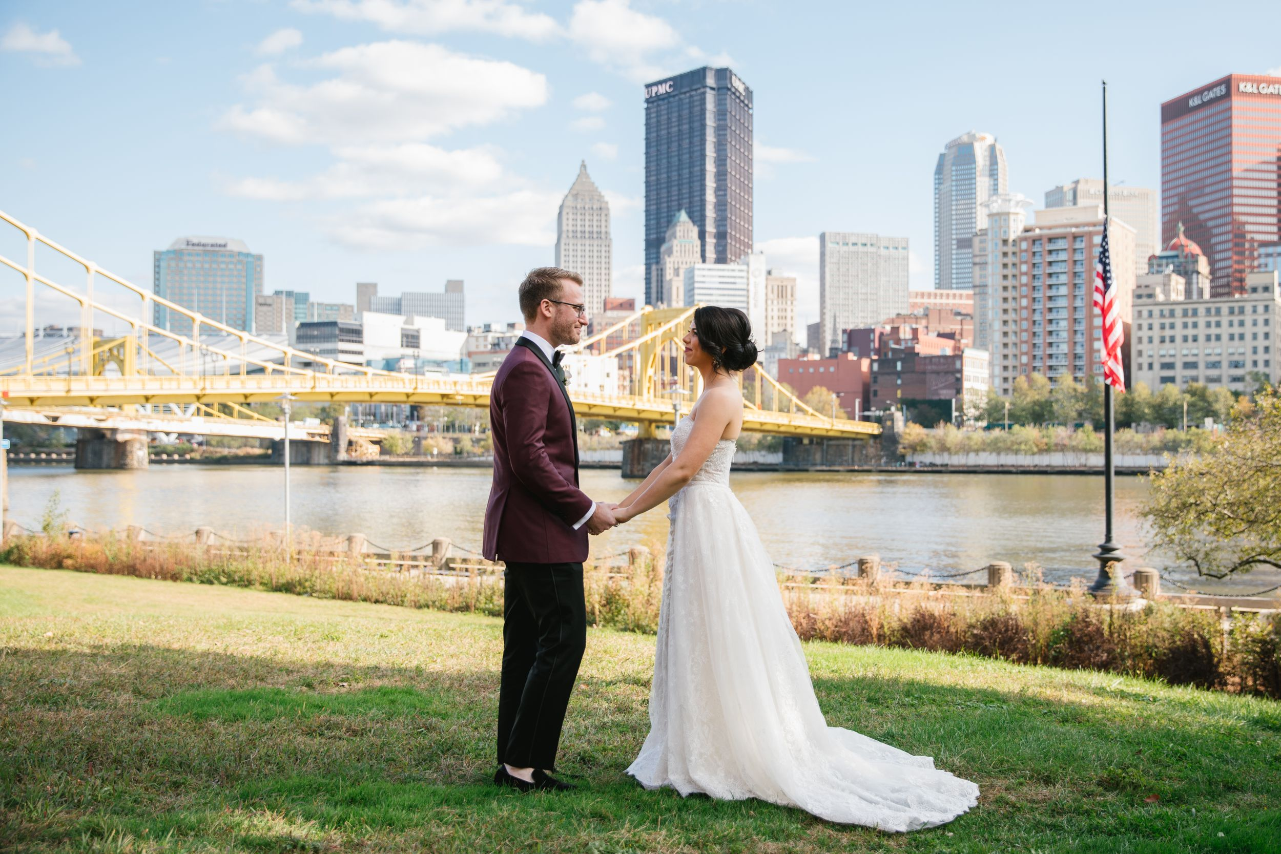 bride and groom holding hands with pittsburgh city behind them