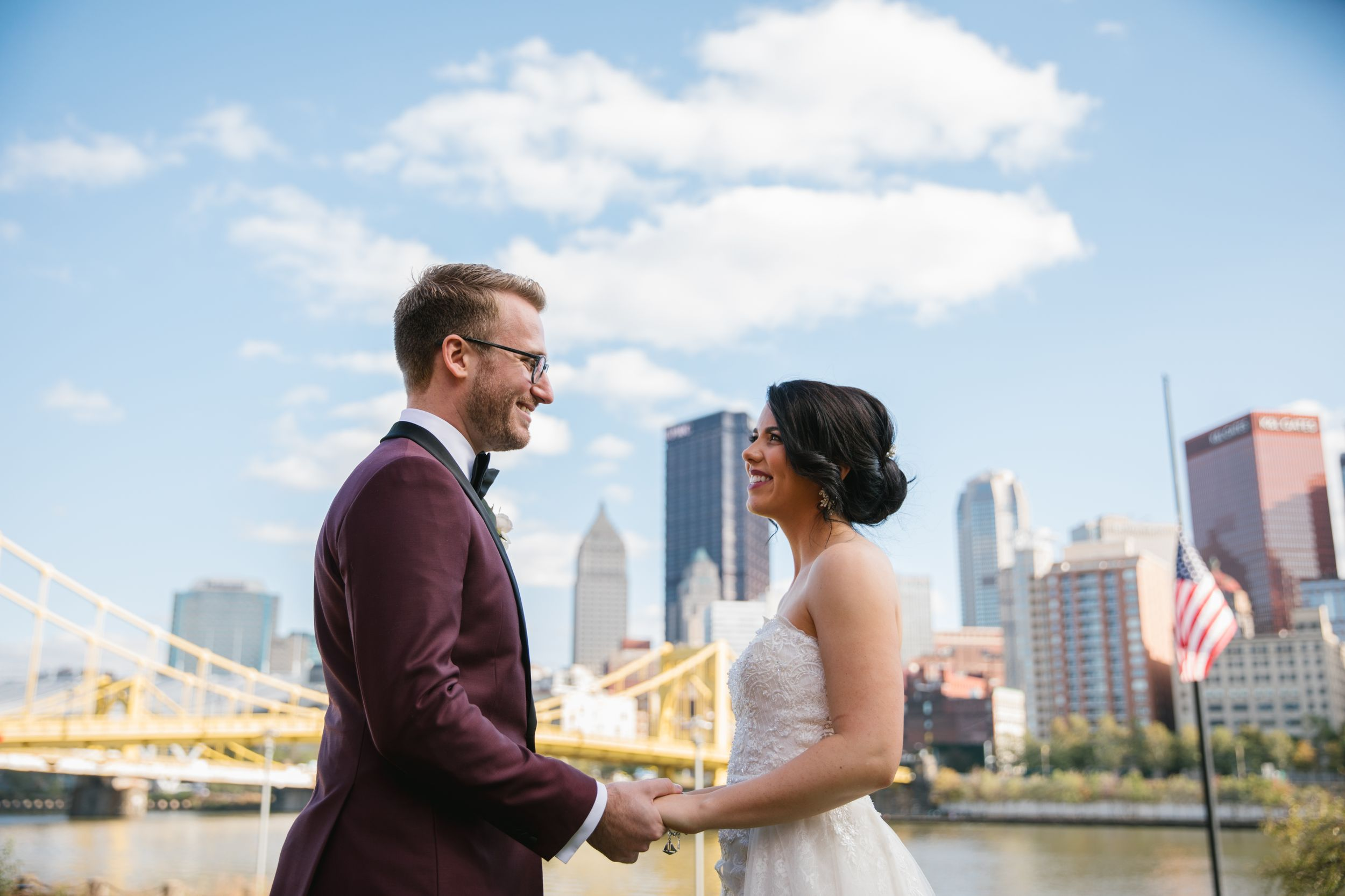 close up of bride and groom holding hands with pittsburgh city behind them