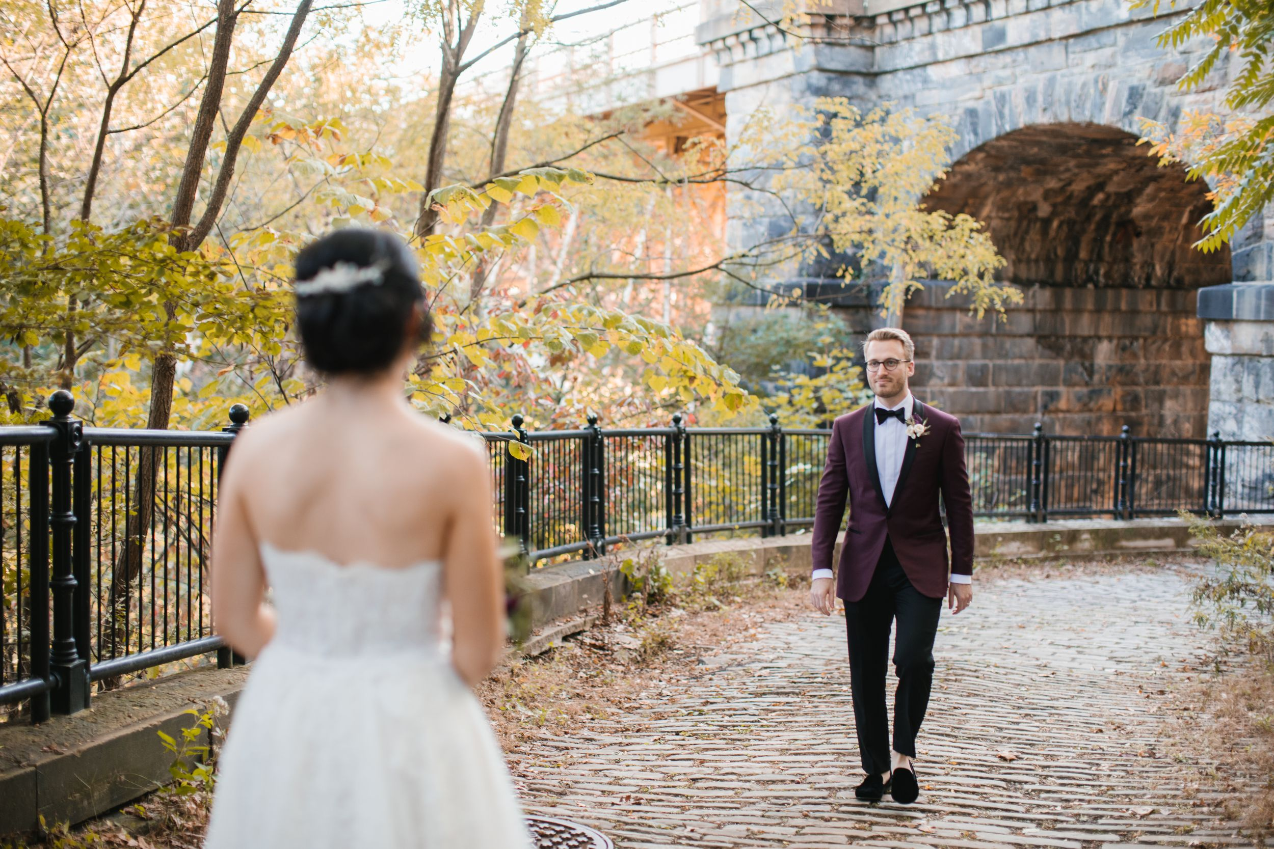 groom walking towards bride in park during fall
