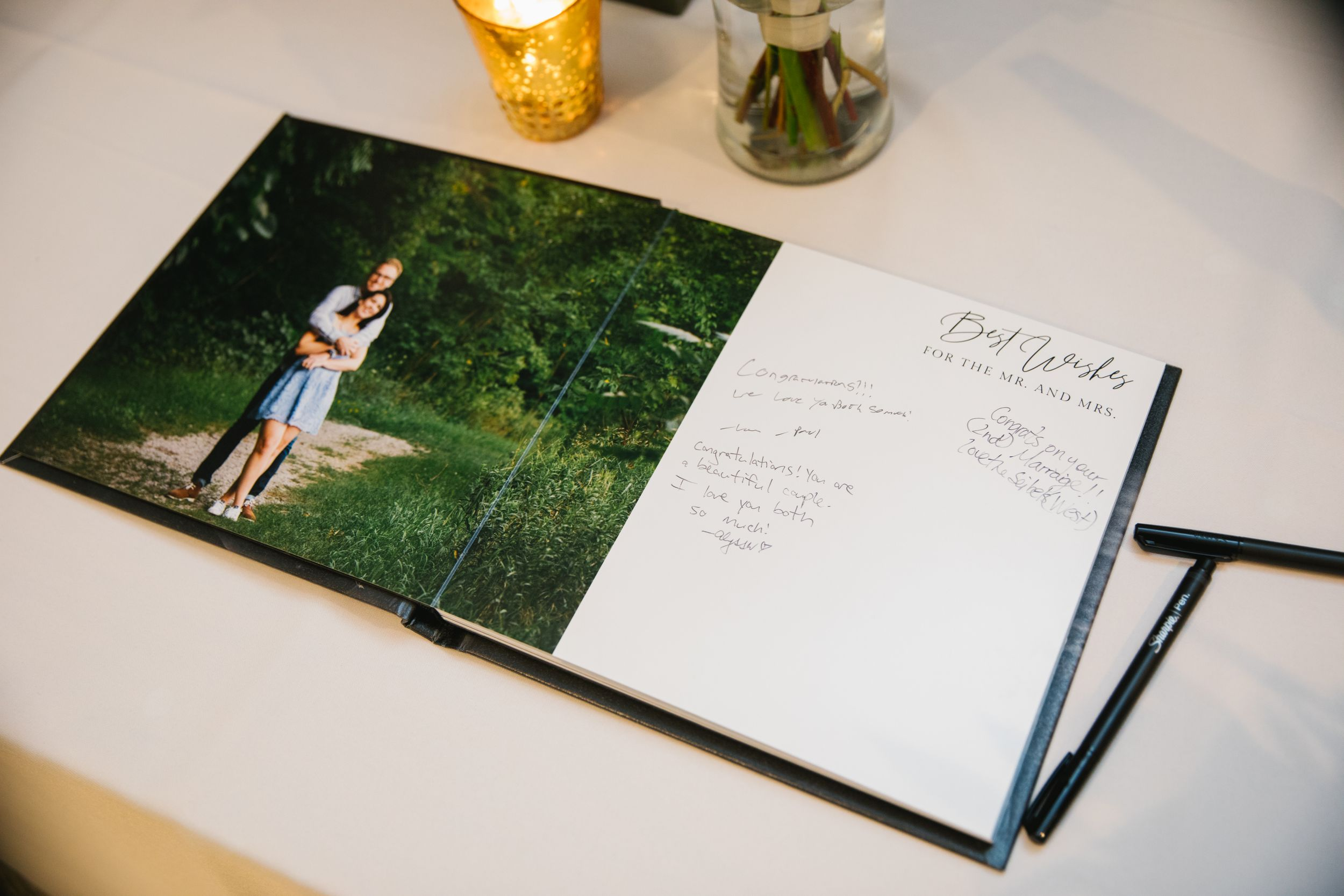 close up of guest signing book with engagement photo and congratulations
