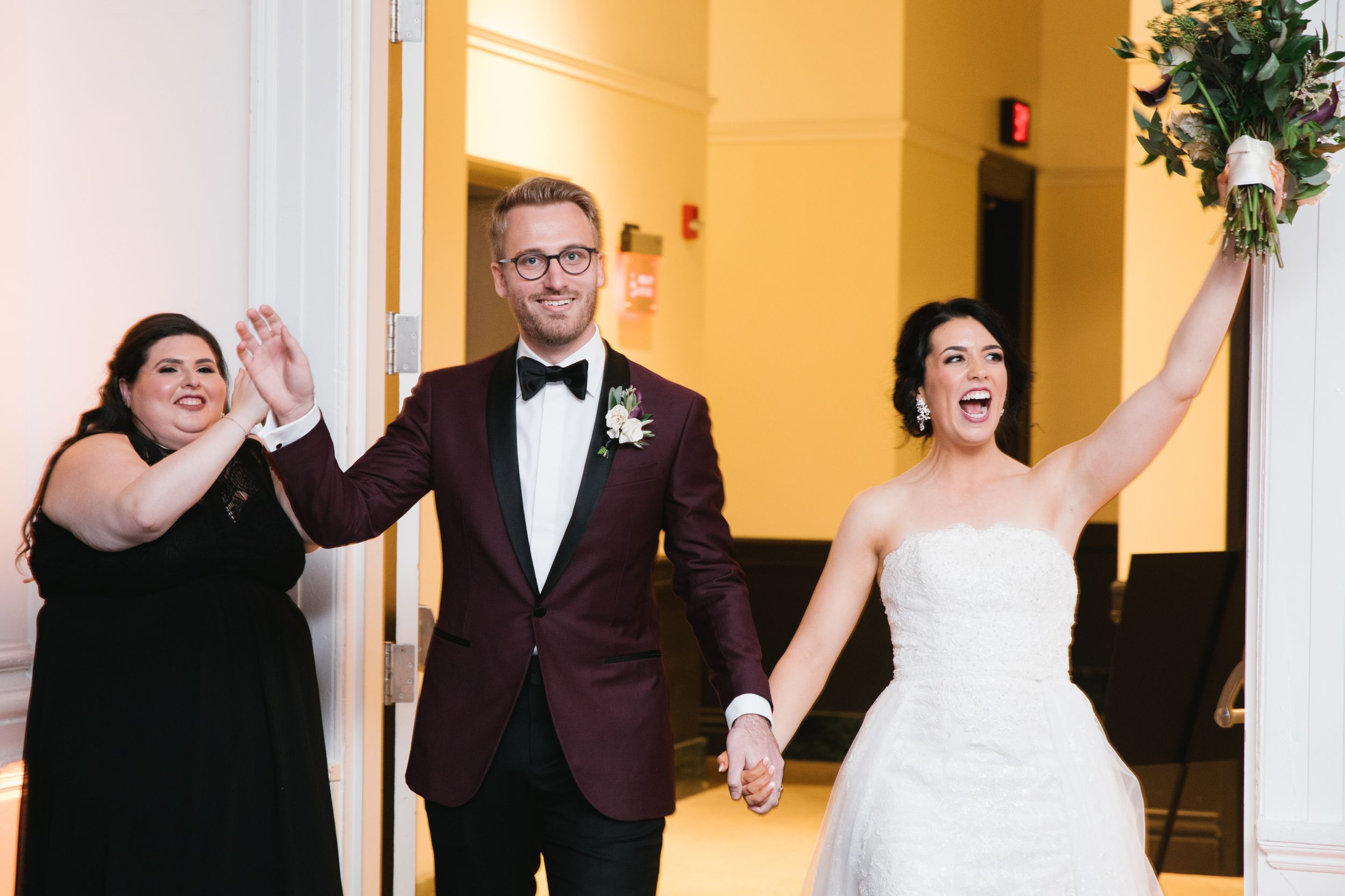 bride and groom enter reception hall with a celebration wedding