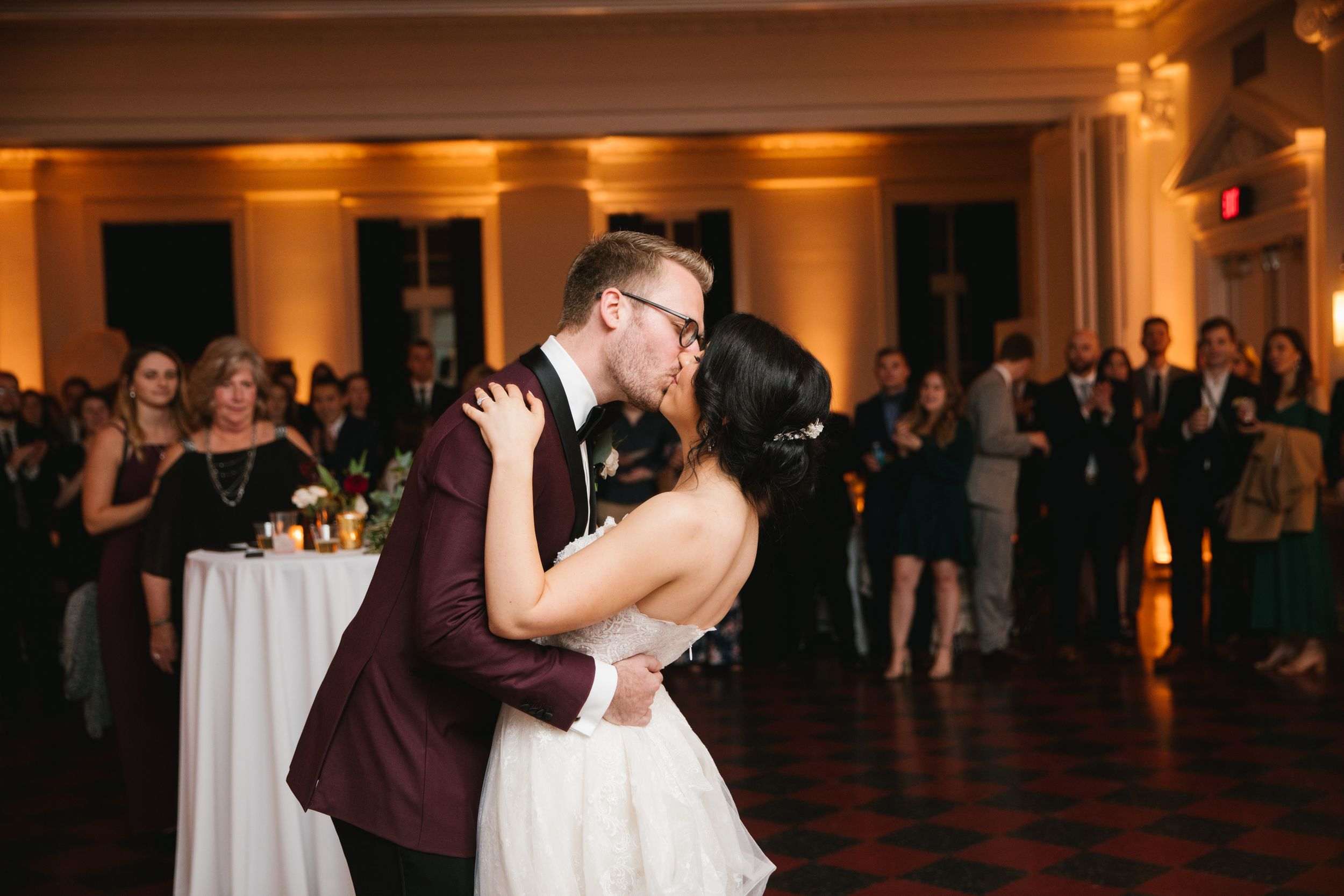 bride and groom kiss during first dance with friends and family behind them