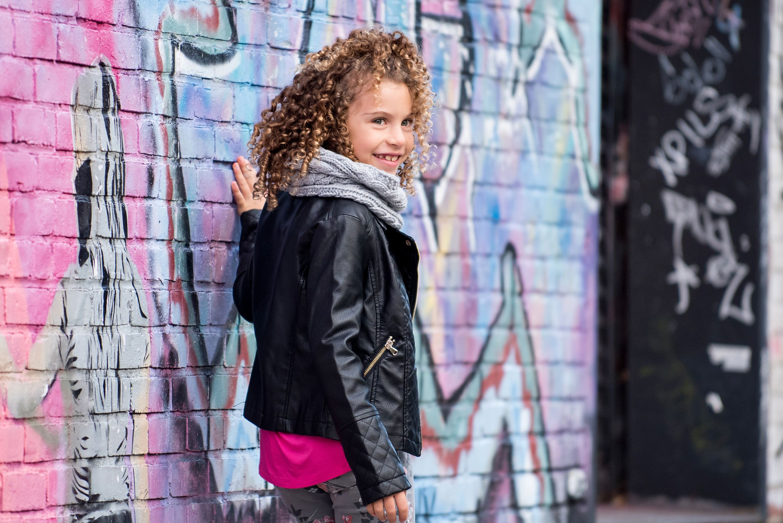 female child model wearing stylish clothes with graffiti background