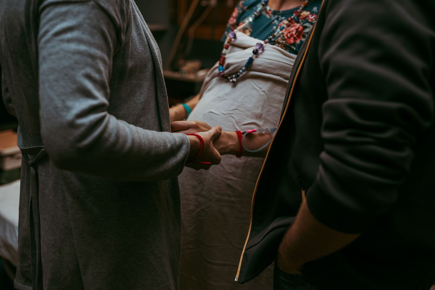 A pregnant woman holding hands with her doula showing both of their prayer bracelets.