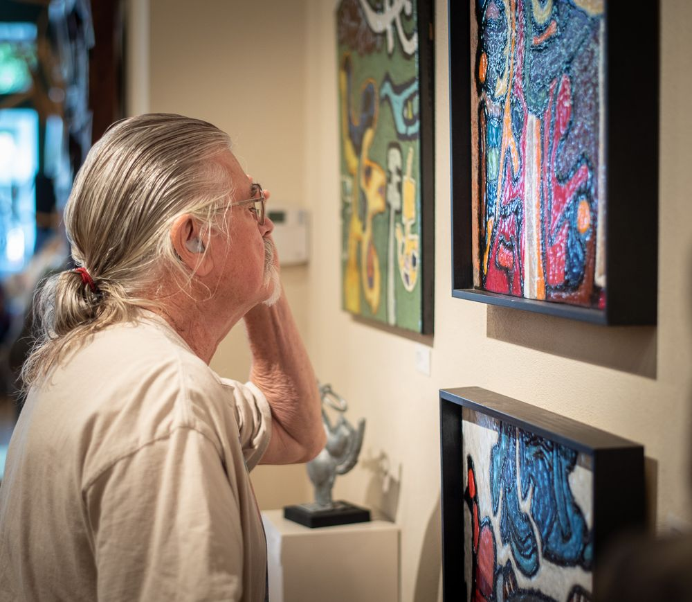 Older man with ponytail peering at a painting on a wall.