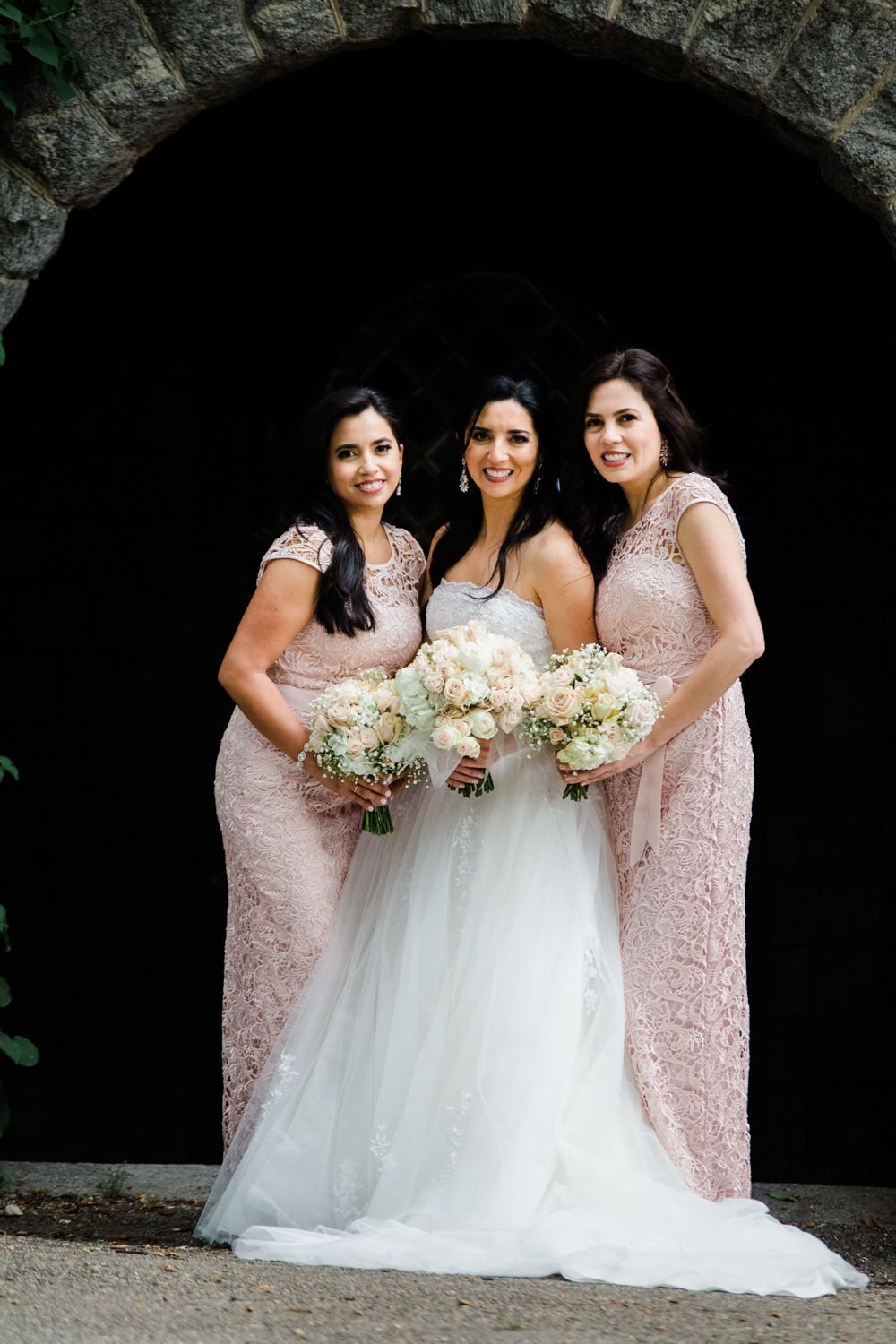 Bride in tulle dress and bridesmaids wearing blush lace