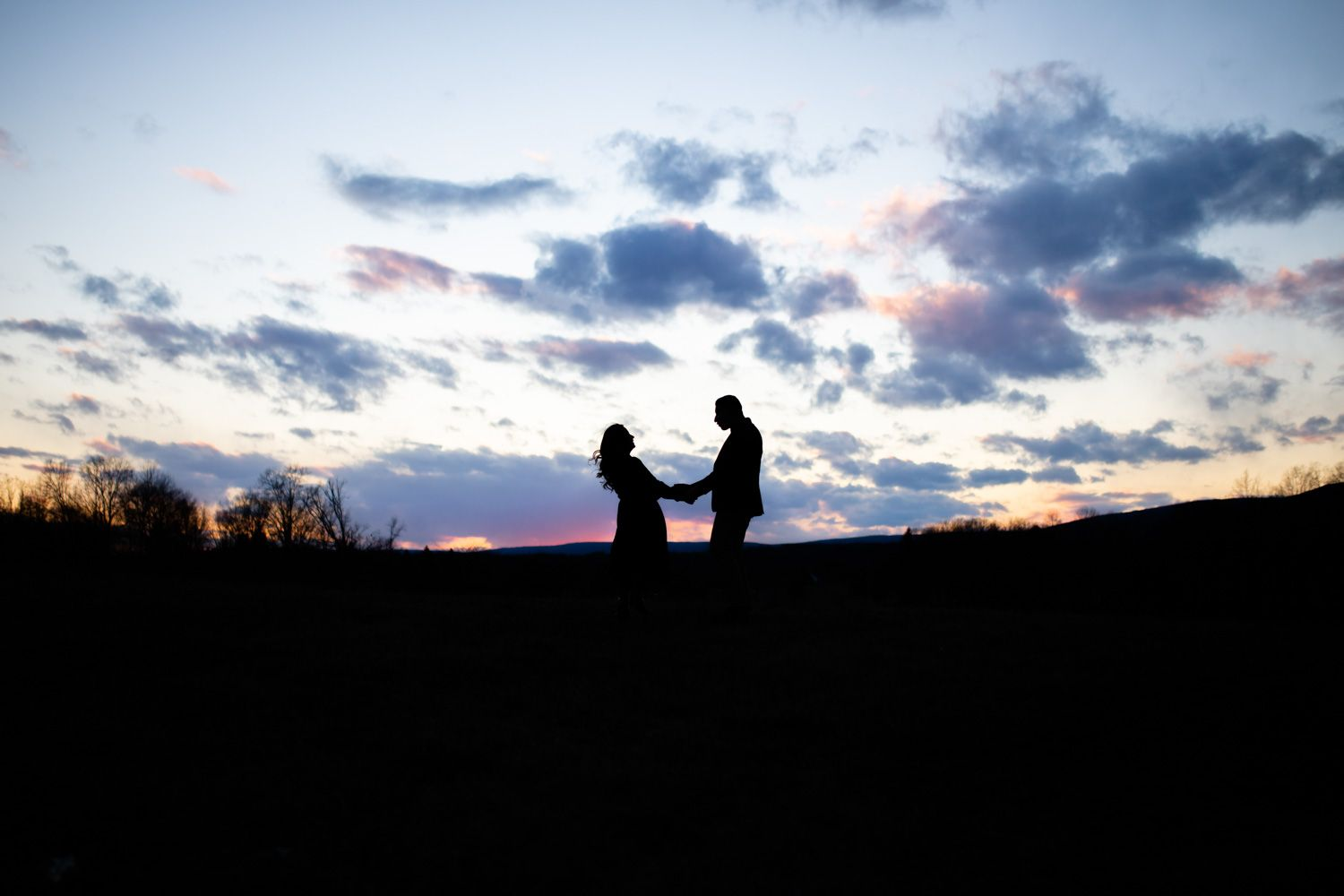 Engaged couple silhouetted by the sunset in the Hudson Valley