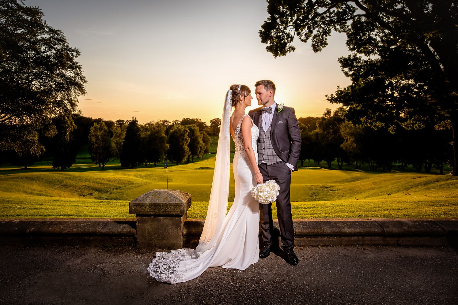 Bride and groom at their Summer wedding, stood before the golf course at Shaw Hill Golf and Spa Hotel in Chorley