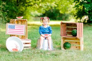 "alt=""Child sitting in Northwest Arkansas field on wooden crate for summer watermelon mini session"""