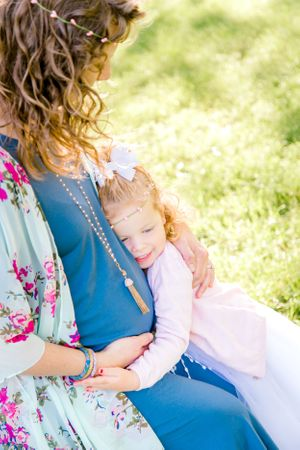 "alt=""Pregant mom and child sitting in Northwest Arkansas field on vintage quilt for Mother's Day maternity portraits"""