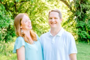 "alt=""Husband and wife laughing during photography session in Northwest Arkansas field for Mother's Day"""