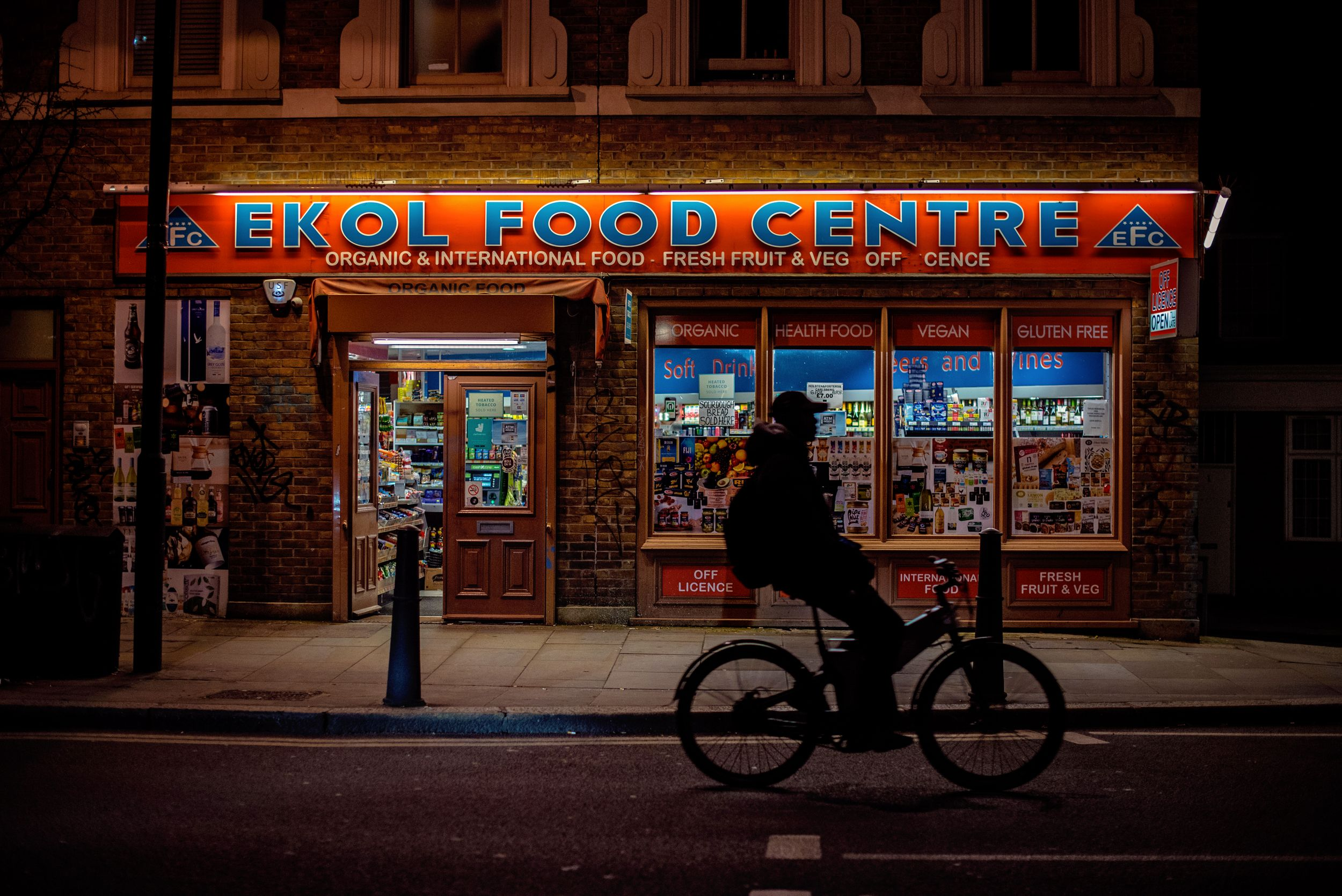 Silhouette of a man riding his bike past lit food centre in London's Shoreditch neighborhood