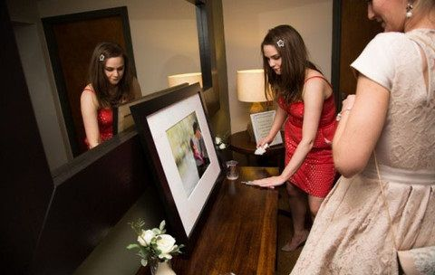 Guests signing wedding guest book and signing frame