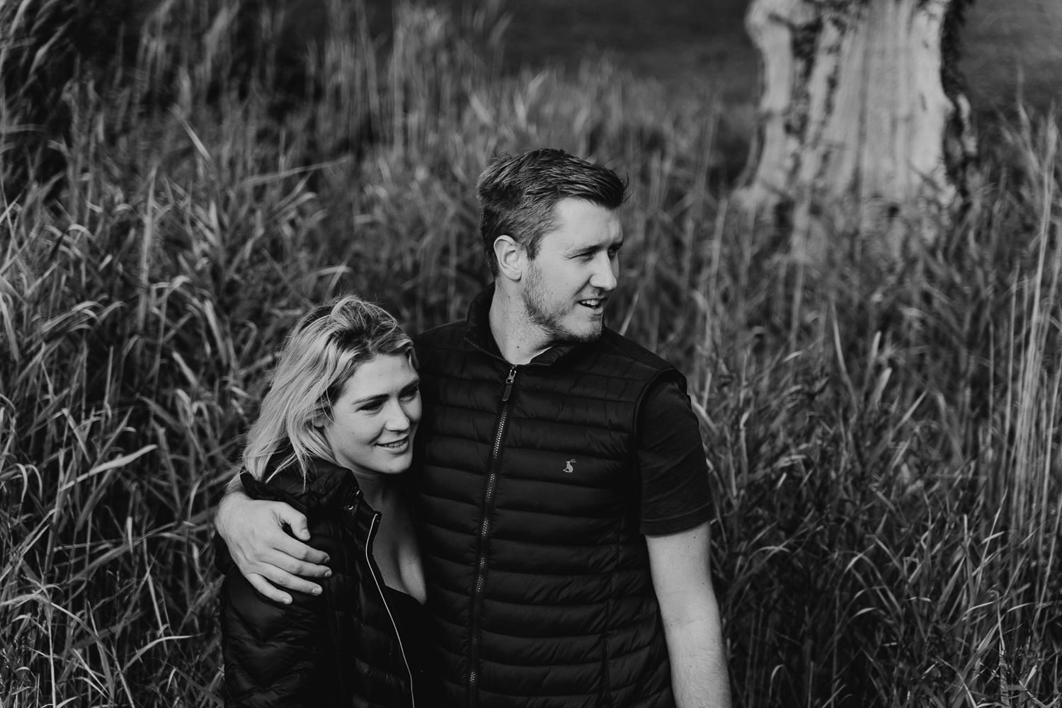 Black and white image, couple cuddle up together in long grass. Katherine and her Camera engagement photoshoot.