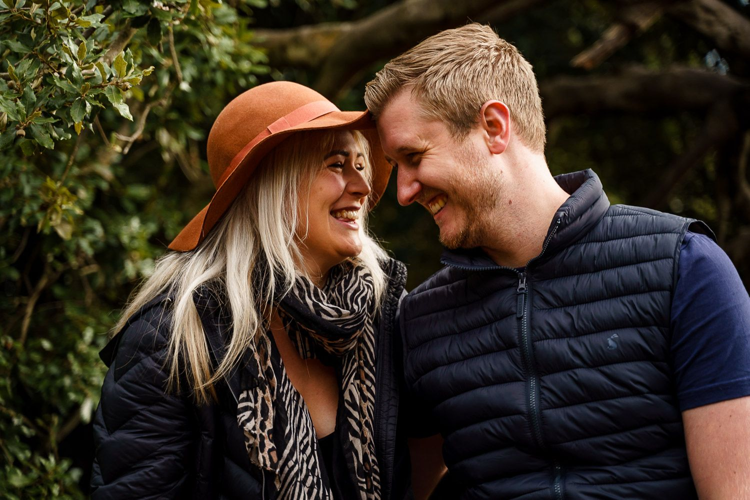 Close up of a couple cuddling up and laughing together in a local park in autumn. Katherine and her Camera