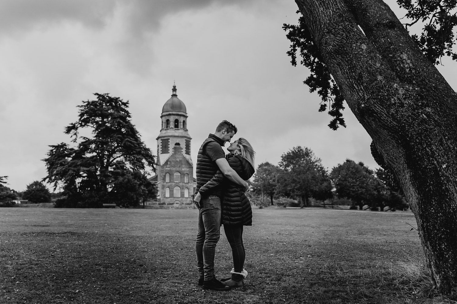 Black and white image of couple stood cuddling in front of Netley Chapel. Katherine and her Camera engagement photoshoot