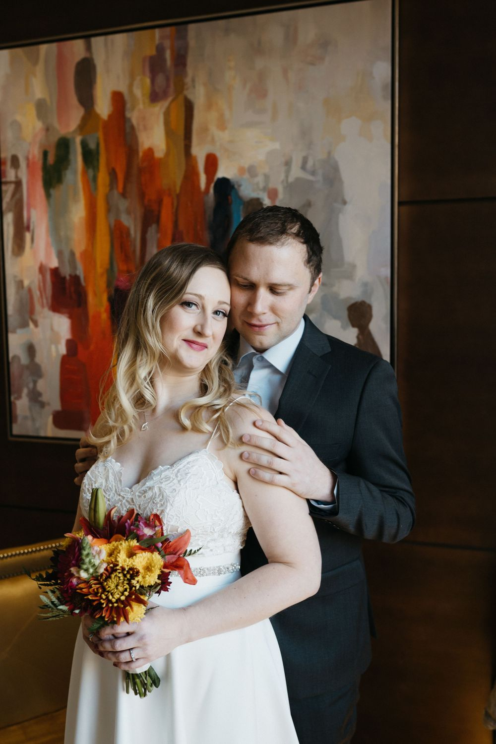 bride-groom-posing-in-front-of-painting-the-republic-on-grand-elopement-desmoines-iowa-raelyn-ramey-photography