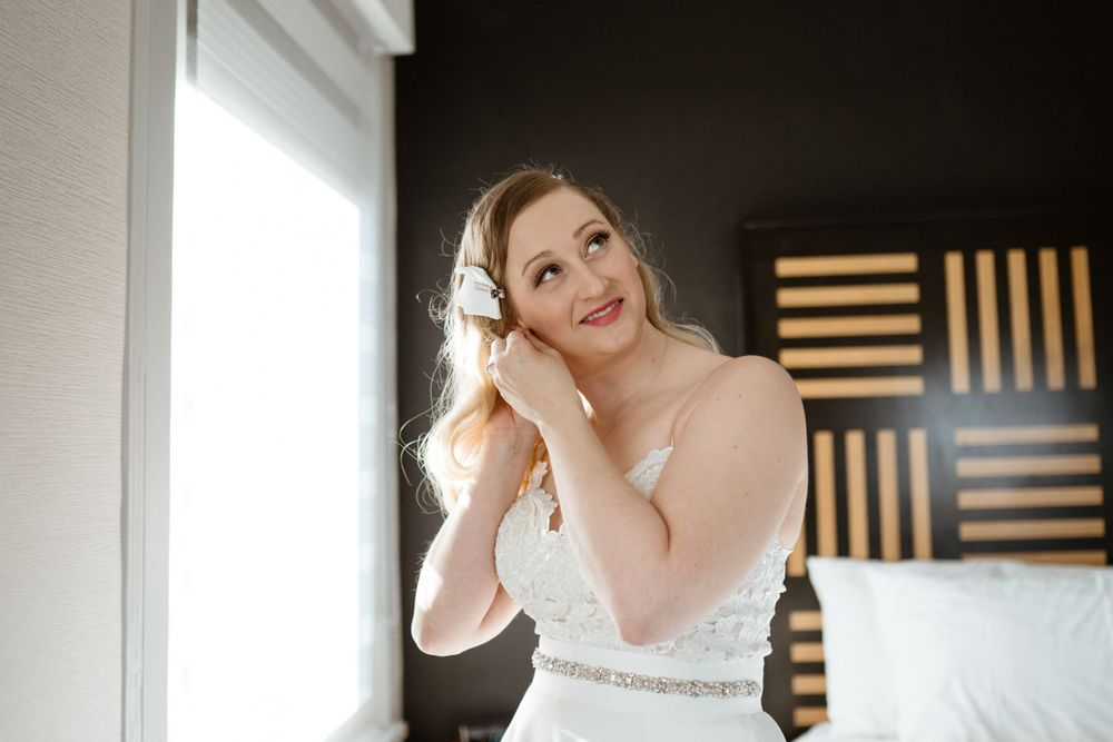 bride-putting-earings-in-getting-ready-savory-hotel-desmoines-iowa-raelyn-ramey-photography