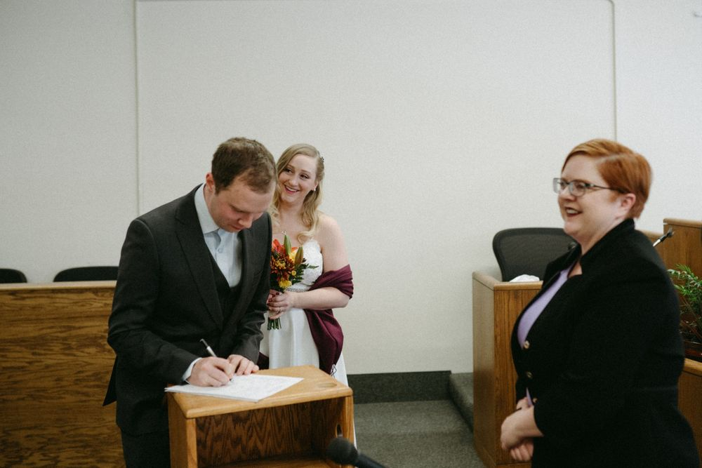 bride-groom-sign-papers-elopement-polk-county-courthouse-desmoines-iowa-raelyn-ramey-photography