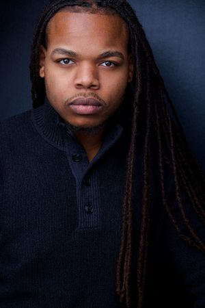 headshots nyc of actor with long black braids against black backdrop