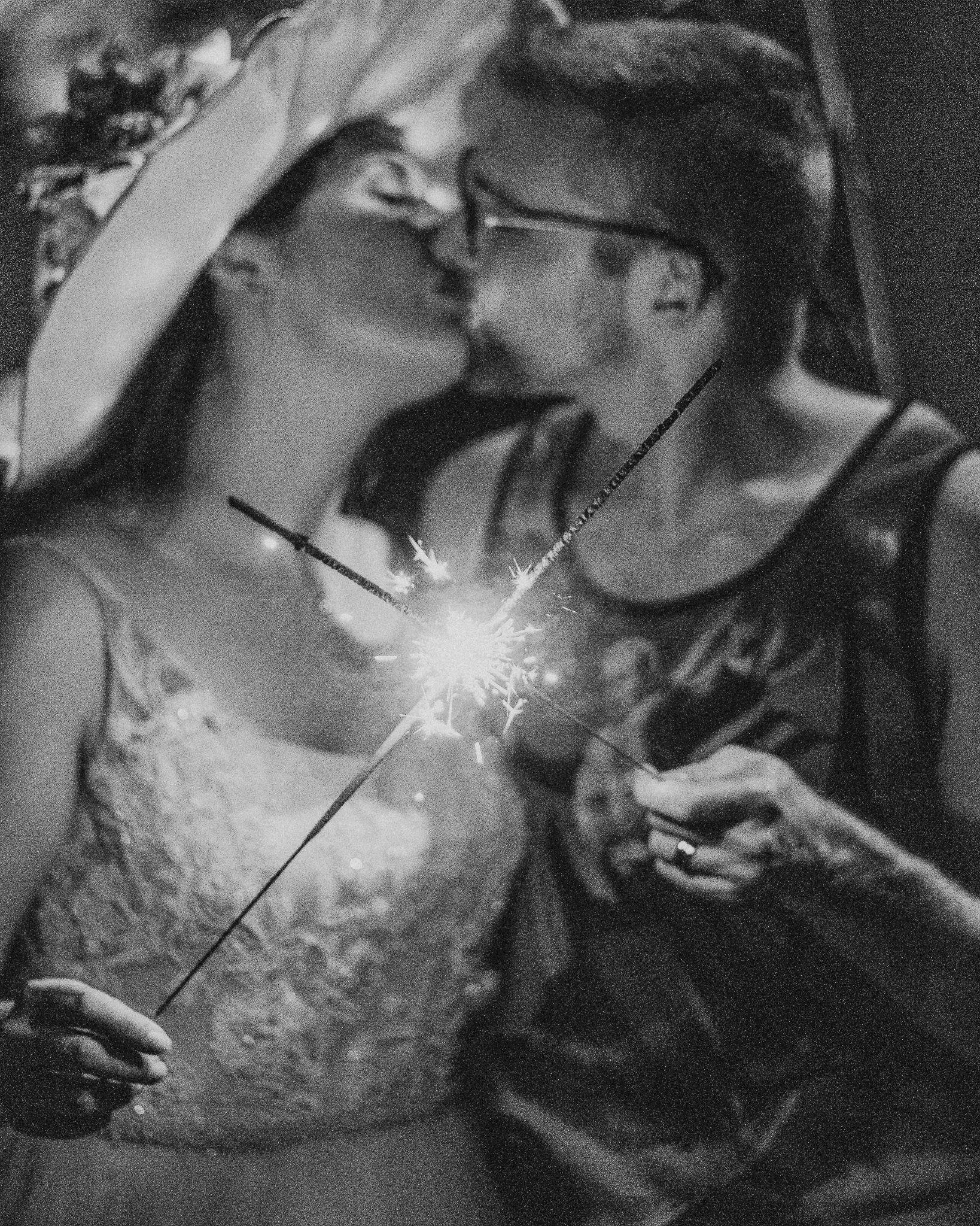 bride and groom kiss as they touch light sparklers together
