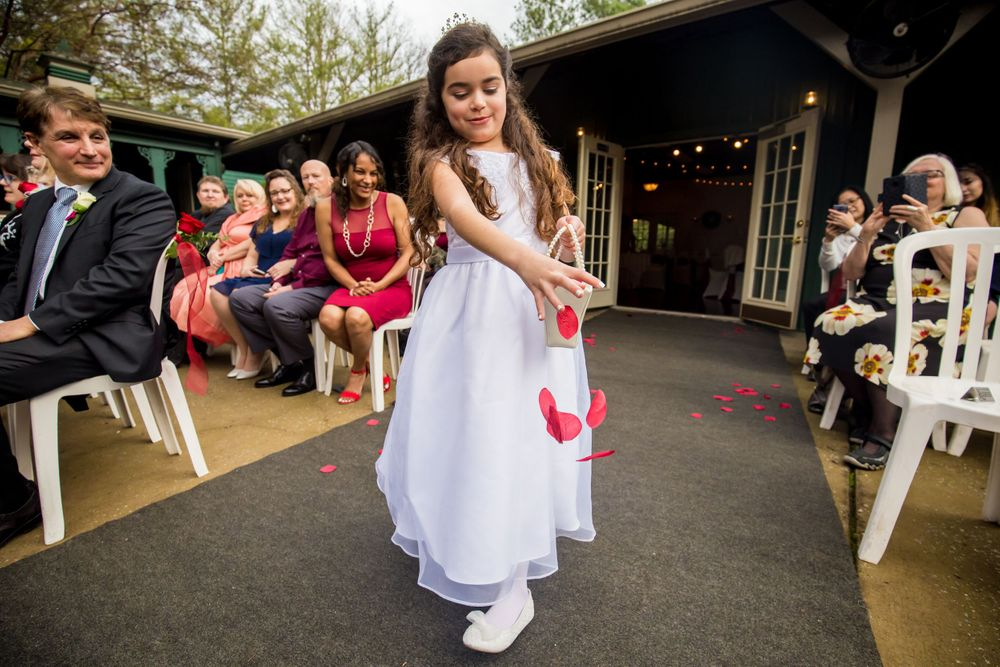 Flower girl spreads flowers on the aisle during a wedding ceremony at Winter Green Woods in Lexington, SC