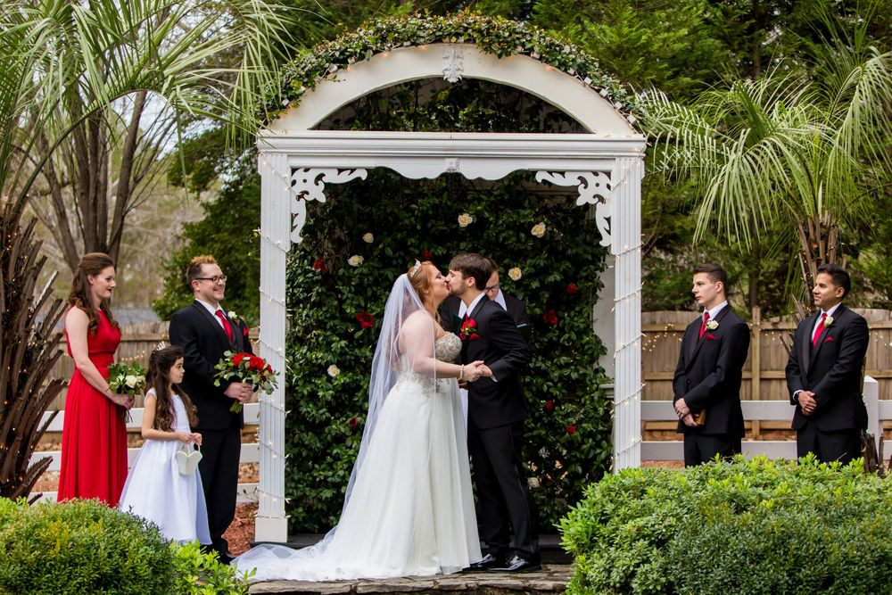 Bride and groom share their first kiss during a wedding ceremony at Winter Green Woods in Lexington, SC