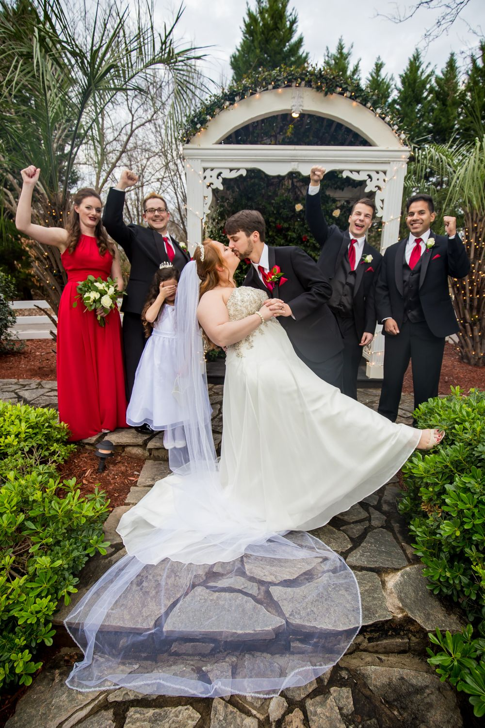 Bride and groom kiss and wedding party cheers during a portrait at Winter Green Woods in Lexington, SC