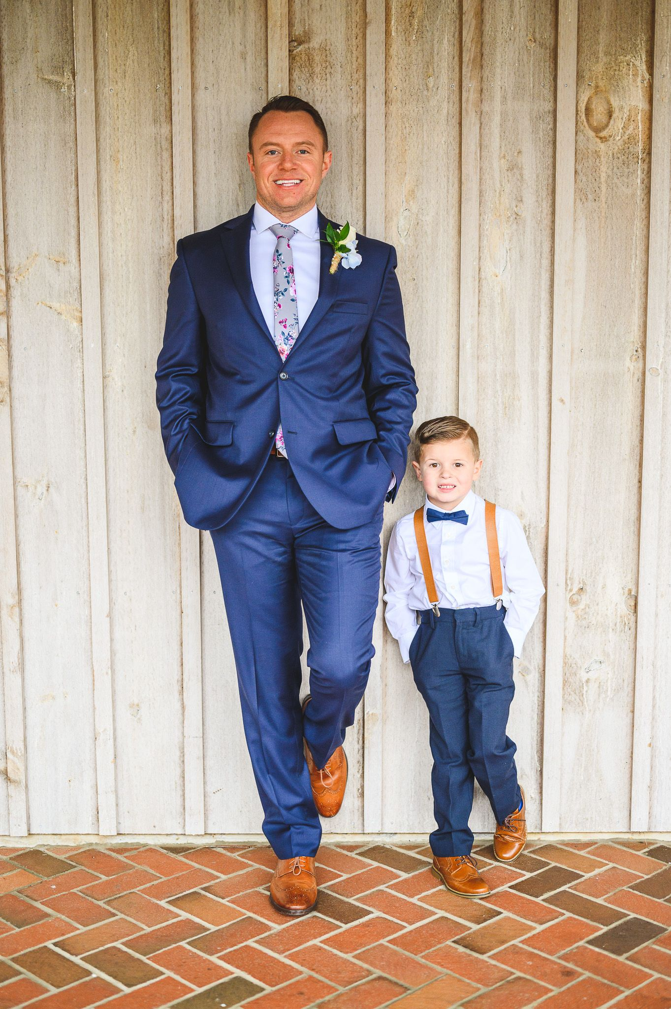 groom and son leading on barn with one leg up at Edel Haus alpaca farm
